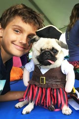 "Ryan Veach with Cocoa, the one eyed wonder pug, won ""Best Overall"" in last year's Mutt March costume contest."