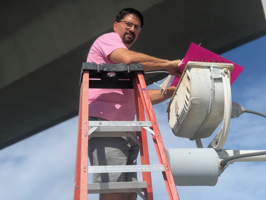 Stuart City Manager David Dyess helps install pink lenses on the lights of the Roosevelt Bridge in Stuart to shine awareness of the courage of breast cancer survivors and those fighting the disease.