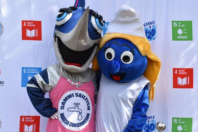 Sammi Sailfish and Smurfette are all smiles about water conservation at the Water Fest in Stuart Memorial Park.