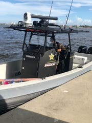 Deputy Robert Peterson of the Martin County Sheriff's Office marine unit piloted the vessel that enabled volunteer installers to reach remove sections of the bridge accessible only by boat.