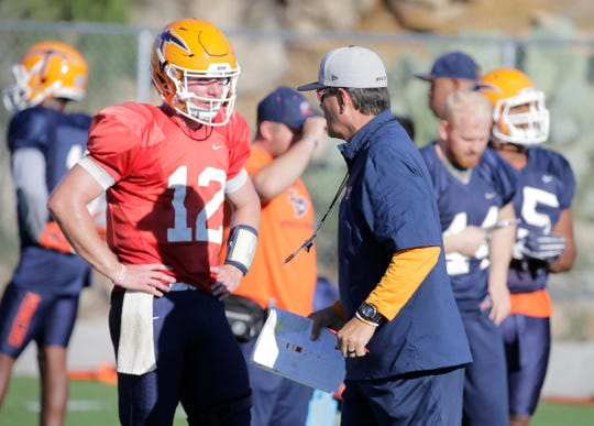 UTEP offensive coordinator/quarterbacks Mike Canales talks to Ryan Metz who looks to be his starting quarterback this Saturday with starting quarterback Kai Locksley nursing a lower left leg injury.