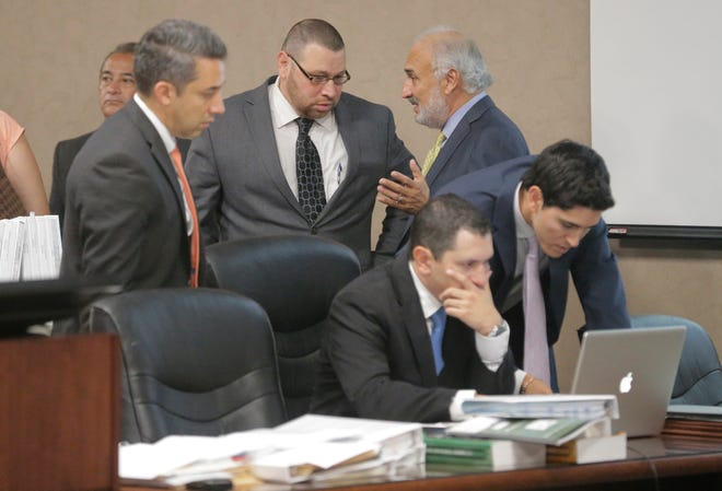 Daniel Villegas, standing at center, speaks with his attorney, Joe Spencer, moments after 409th District Judge Sam Medrano broke for lunch Wednesday morning.