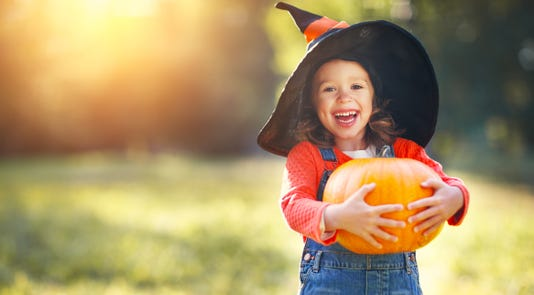Child Girl With Pumpkin Outdoors In Halloween