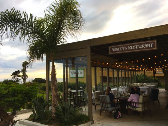 Diners enjoy the beginning of a sunset from the sheltered patio at Austen's Restaurant on the grounds of Ventura's historic Pierpont Inn.