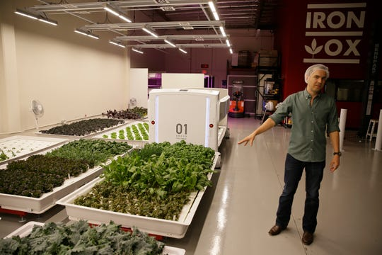 In this Sept. 27 photo, Iron Ox CEO Brandon Alexander gives a tour at his robotic indoor farm in San Carlos, Calif. Alexander spent a lot of time working his family's farm in Oklahoma before he headed off to the University of Texas to study robotics.