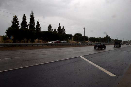 Cars drive along a wet Highway 101 in Camarillo as light rain falls Tuesday afternoon.