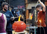 Wheaton Arts Studio Manager Skitch Manion and his staff work on a glass pumpkin during a demonstration in Millville on Wednesday, October 3, 2018.