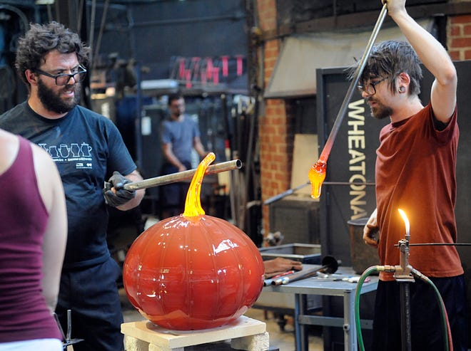 From left to right, glass studio manager Skitch Manion and studio assistant Brian Reilly work together making a large glass pumpkin during a demonstration at Wheaton Arts in Millville.