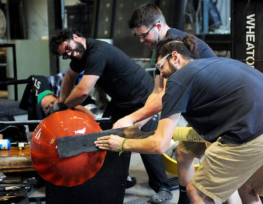 From left to right, Wheaton Arts Studio Manager Skitch Manion, studio assistant John Roesberg and studio intern Max Hertzan work together on making a large glass pumpkin during a glass blowing demonstration in Millville on Wednesday, October 3.