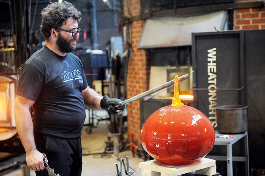 Wheaton Arts Studio Manager Skitch Manion works on the stem of a large glass pumpkin during a public demonstration in Millville.