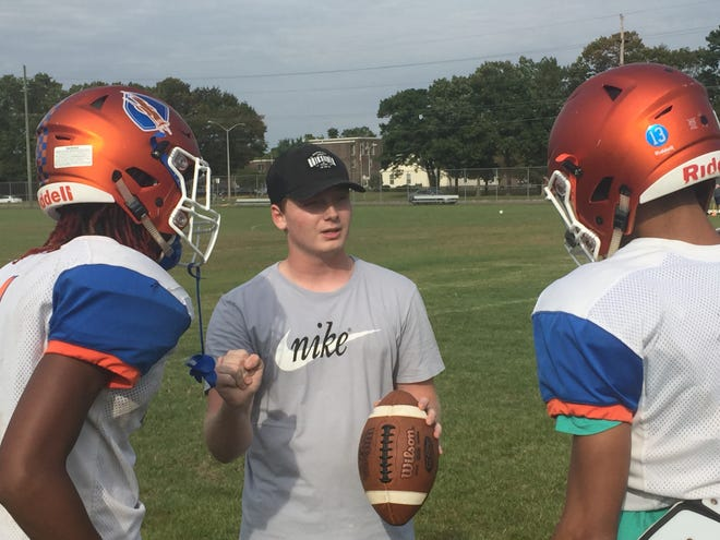 Millville quarterback coach Tristan Harris, center, goes through instruction with Maurice Smith, left, and Eddie Jamison during a recent practice. Harris is a volunteer coach with the Thunderbolts.