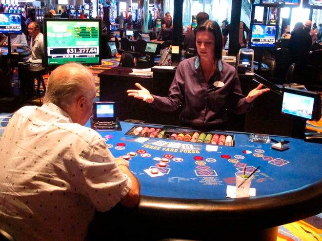 A dealer shows that her hands are empty during a card game at the Ocean Resort Casino in Atlantic City.