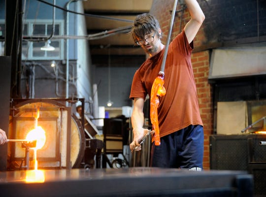 Brian Reilly, studio assistant at Wheaton Arts, is one of five people helping to create a large glass pumpkin during a public demonstration.