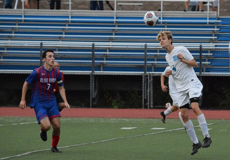 Rye Neck sweeper Thomas Crook heads the ball away from Blind Brook midfielder Zach Kornblum during a 0-0 tie on Tuesday, Oct. 2, 2018.