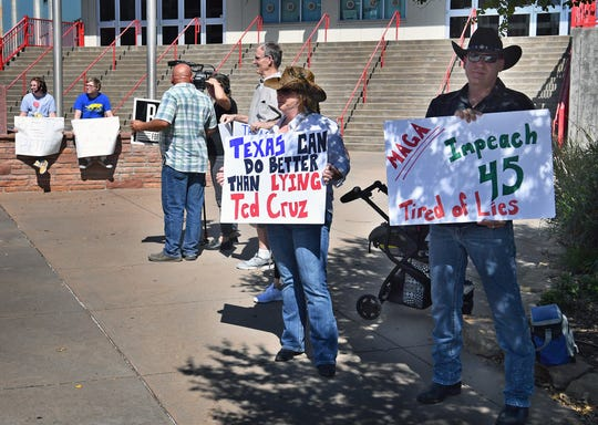 Protestors hold signs outside a Senator Ted Cruz rally Wednesday at the Ray Clymer Exhibit Hall in Wichita Falls, Texas. Donald Trump Jr. also campaigned for Cruz at the event.