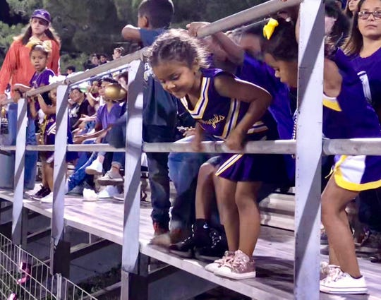 Munday kids watch the football game from the stands Saturday night.