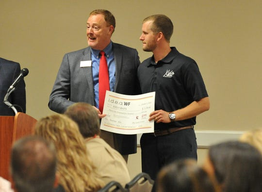 In this file photo, Dr. Scott Manley, left, gives Leland Wetzel of Xylo Bats, LLC, his award during a i.d.e.a.WF ceremony. Manley said there are many programs available through the Dillard College to help businesses and nonprofits.