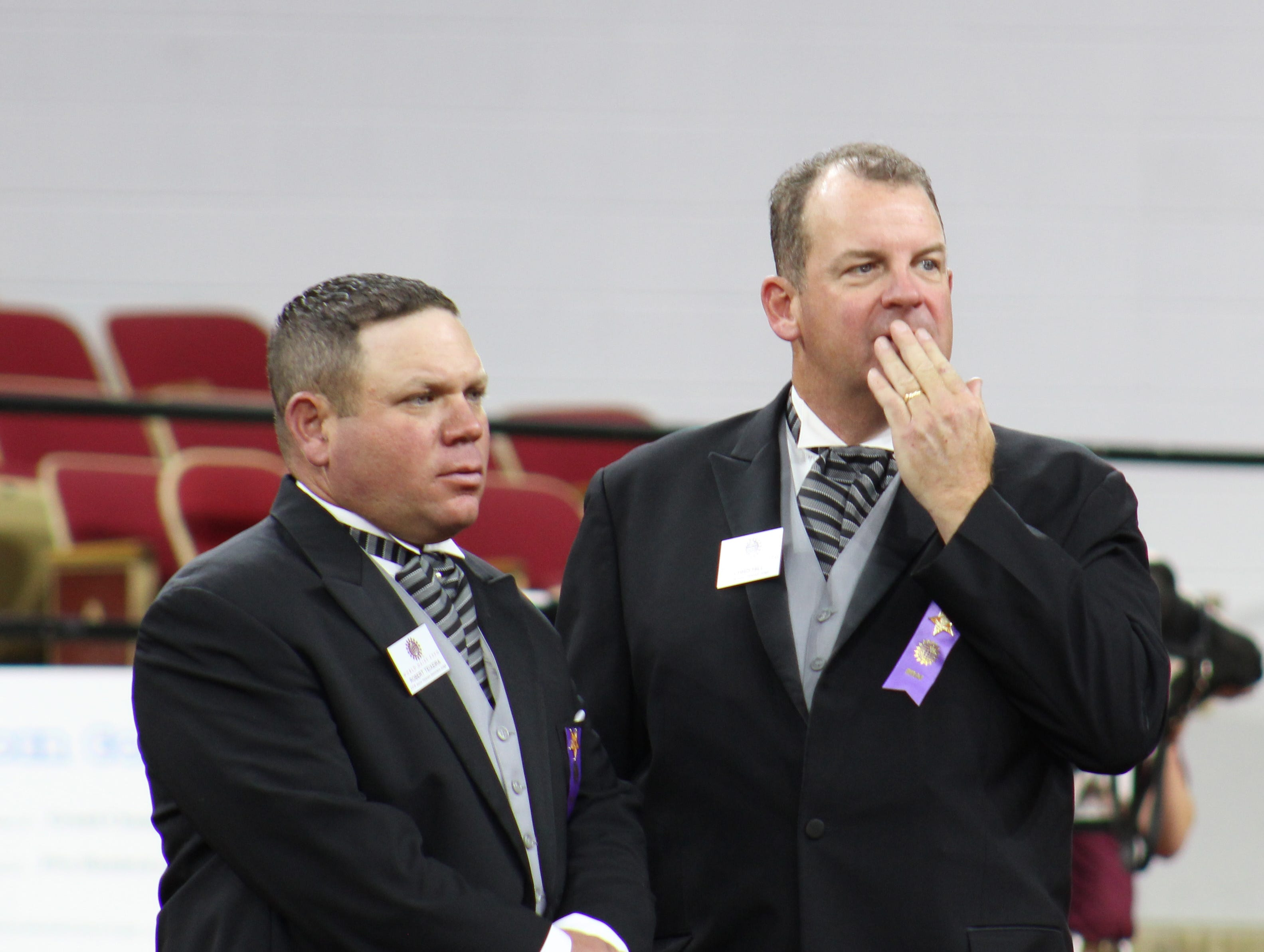 Associate judge Robert Teixeira (left) head judge Chris Hill confer before making their final placing in a class during the International Junior Holstein Show.