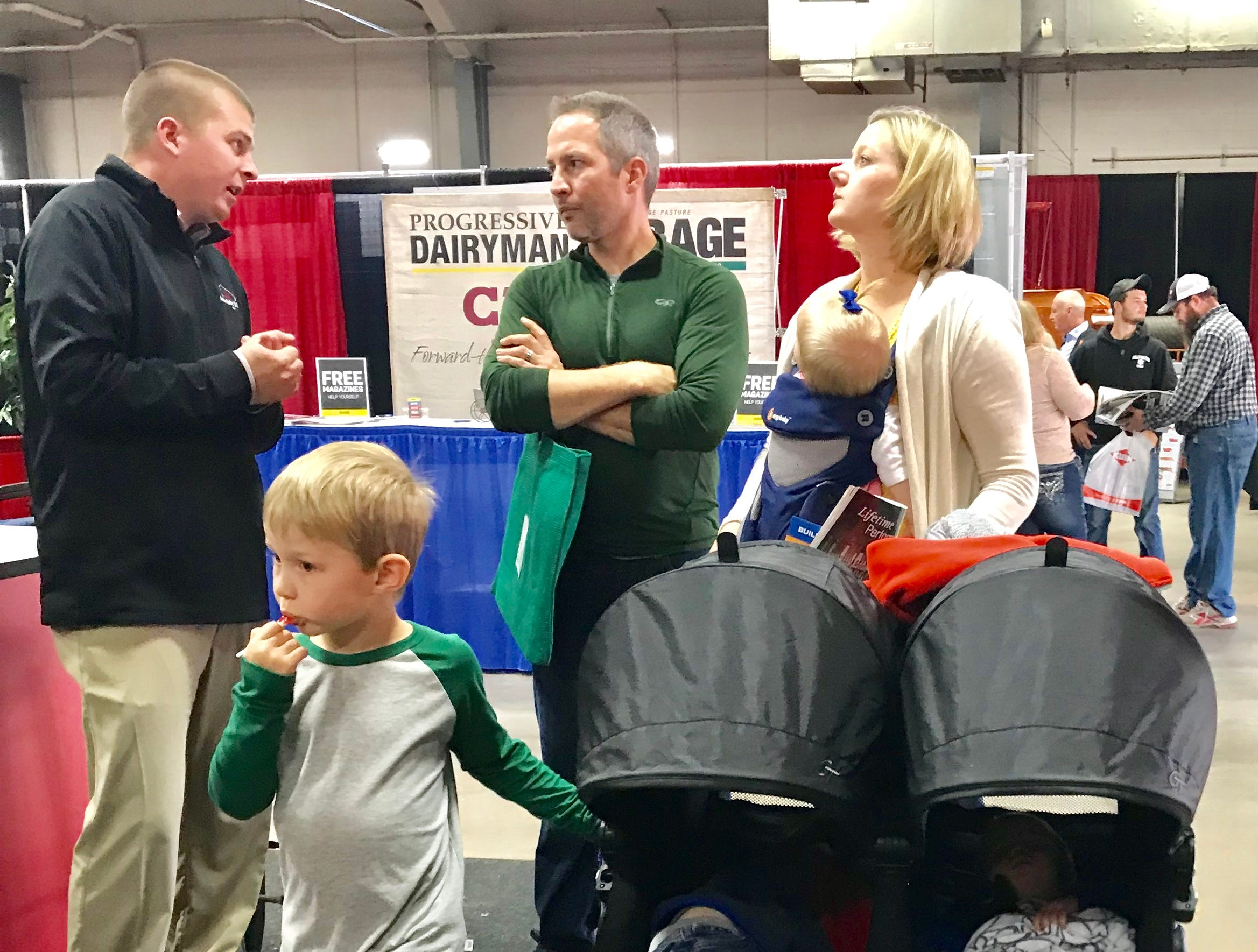 Three of their four children take a snooze while these parents talk shop with an exhibitor inside the arena.