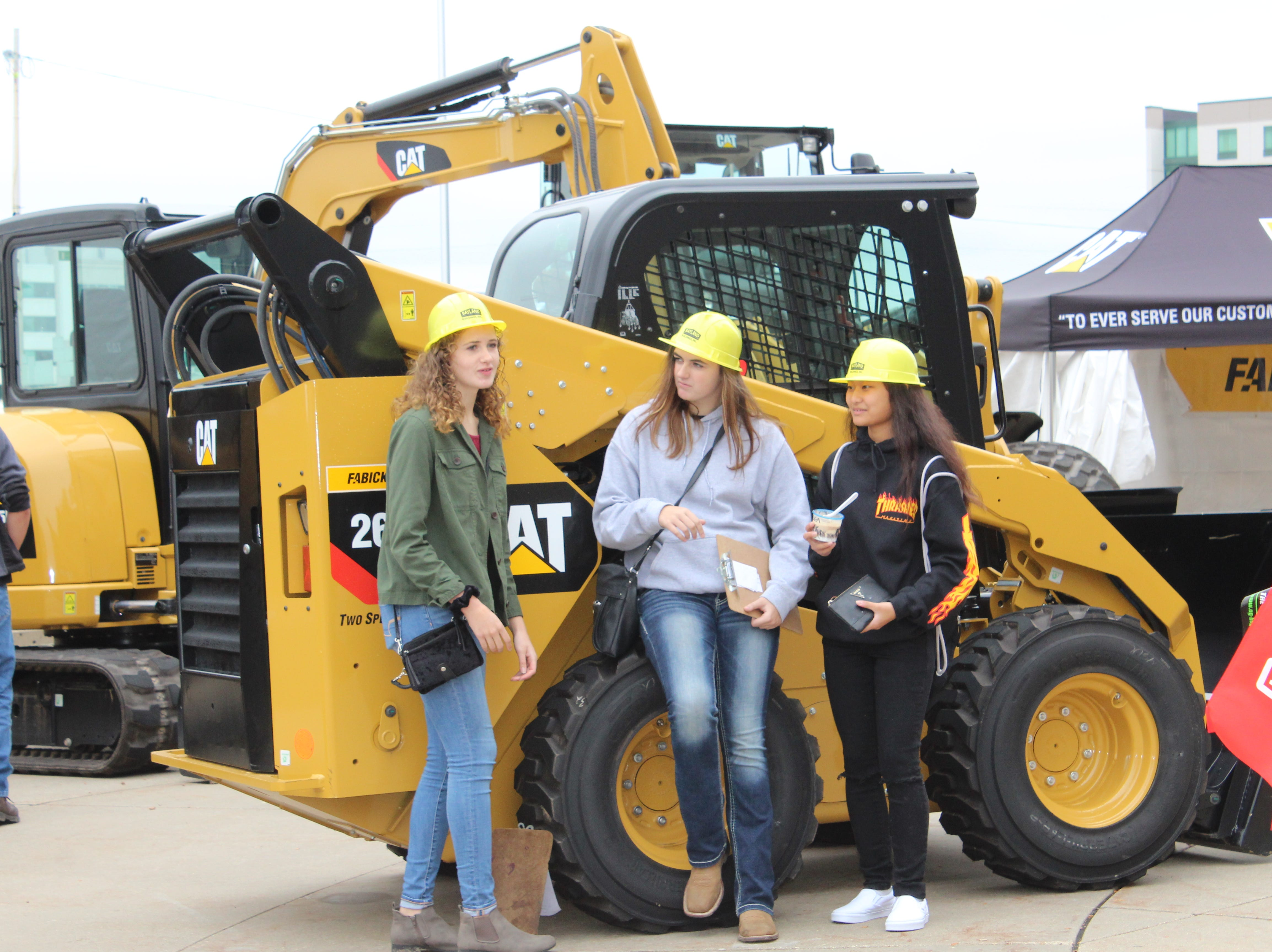 This trio sports hard hats at the Caterpillar exhibit outside the Exhibition Hall.