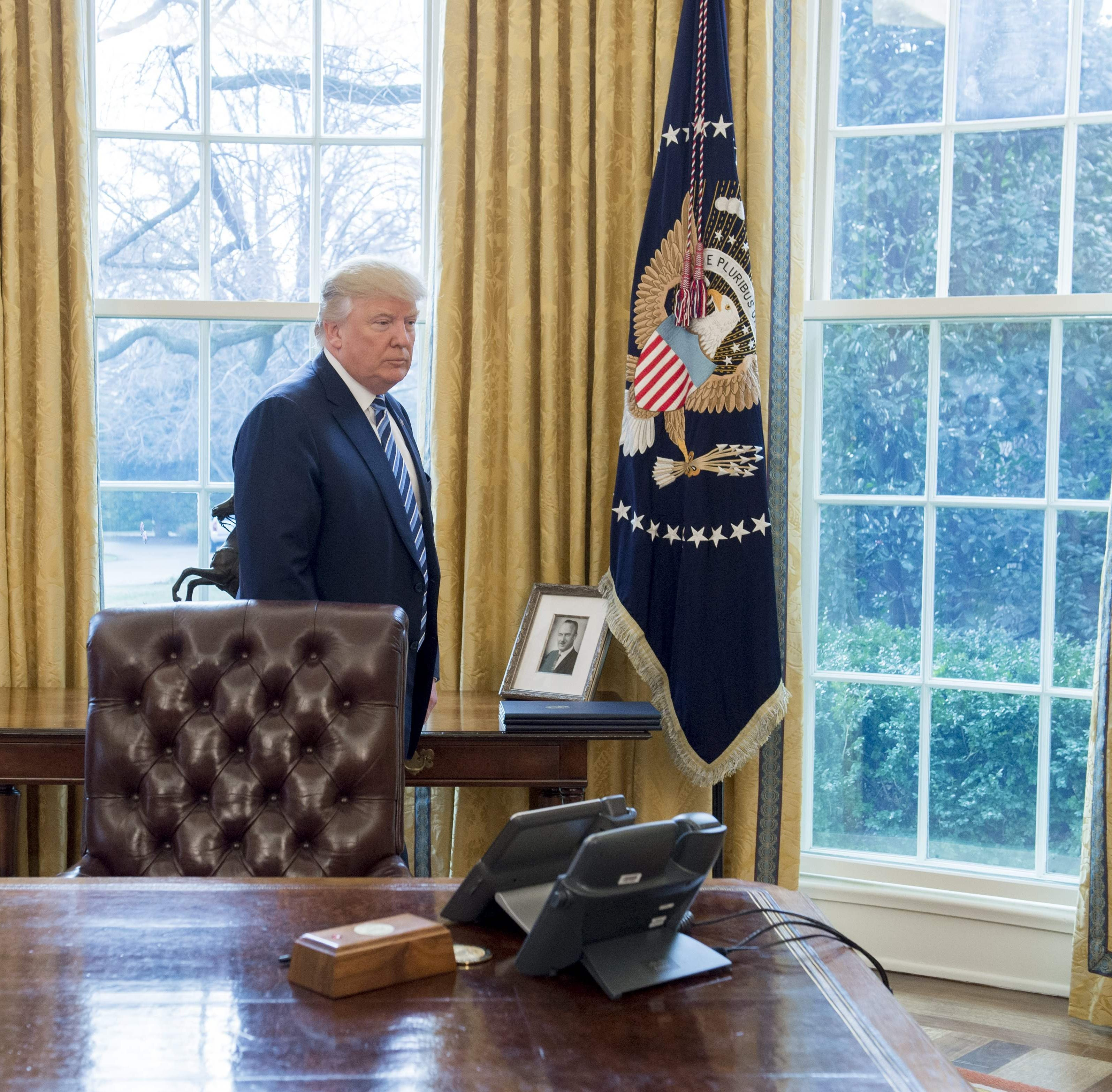President Donald Trump with a photo of his father, Fred Trump, in the Oval Office on Feb. 09, 2017.