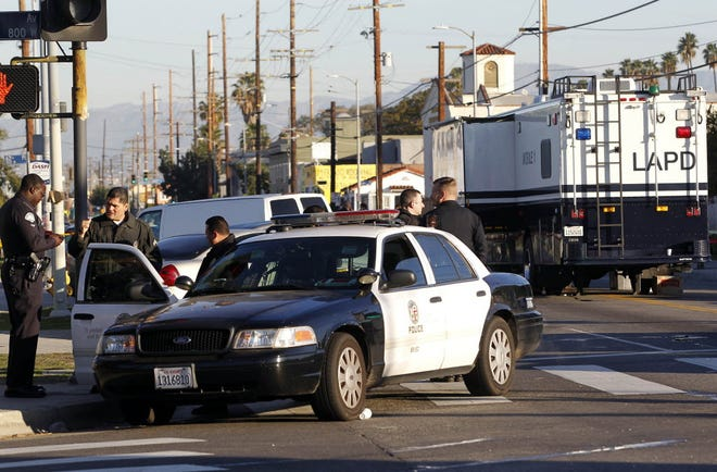 Los Angeles police officers investigate a shooting in 2014.