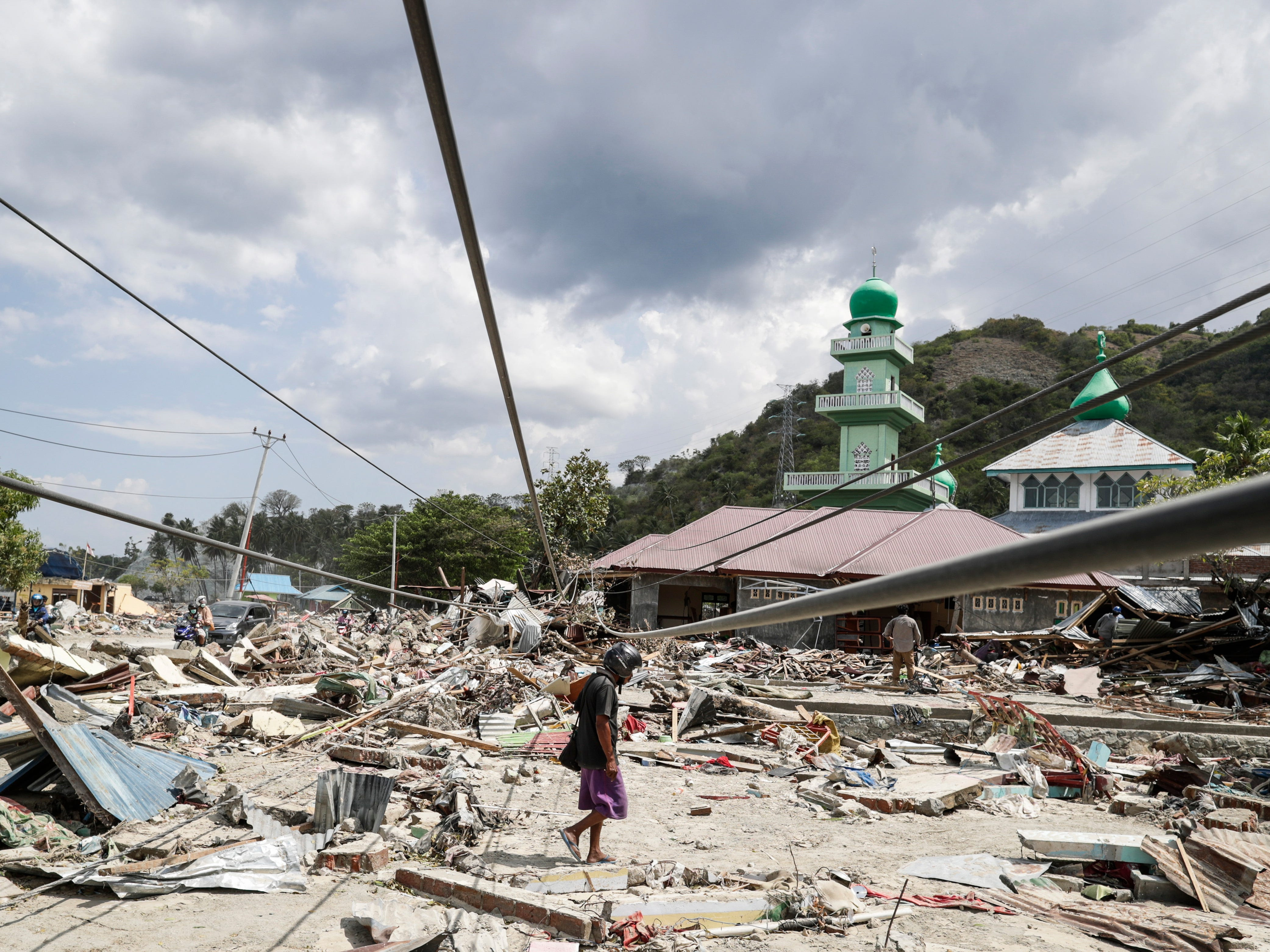 An Indonesian man walks on the rubble at a tsunami devastated area in Donggala, Central Sulawesi, Indonesia, Oct. 3 2018.
