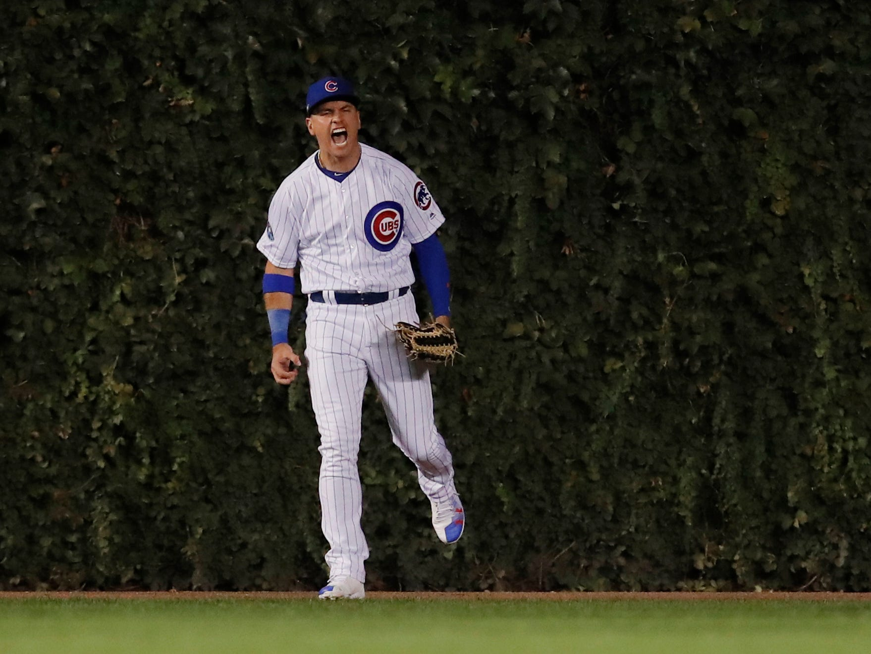 NL wild card: Cubs center fielder Albert Almora Jr. makes a catch up against the ivy hit by Rockies' David Dahl.
