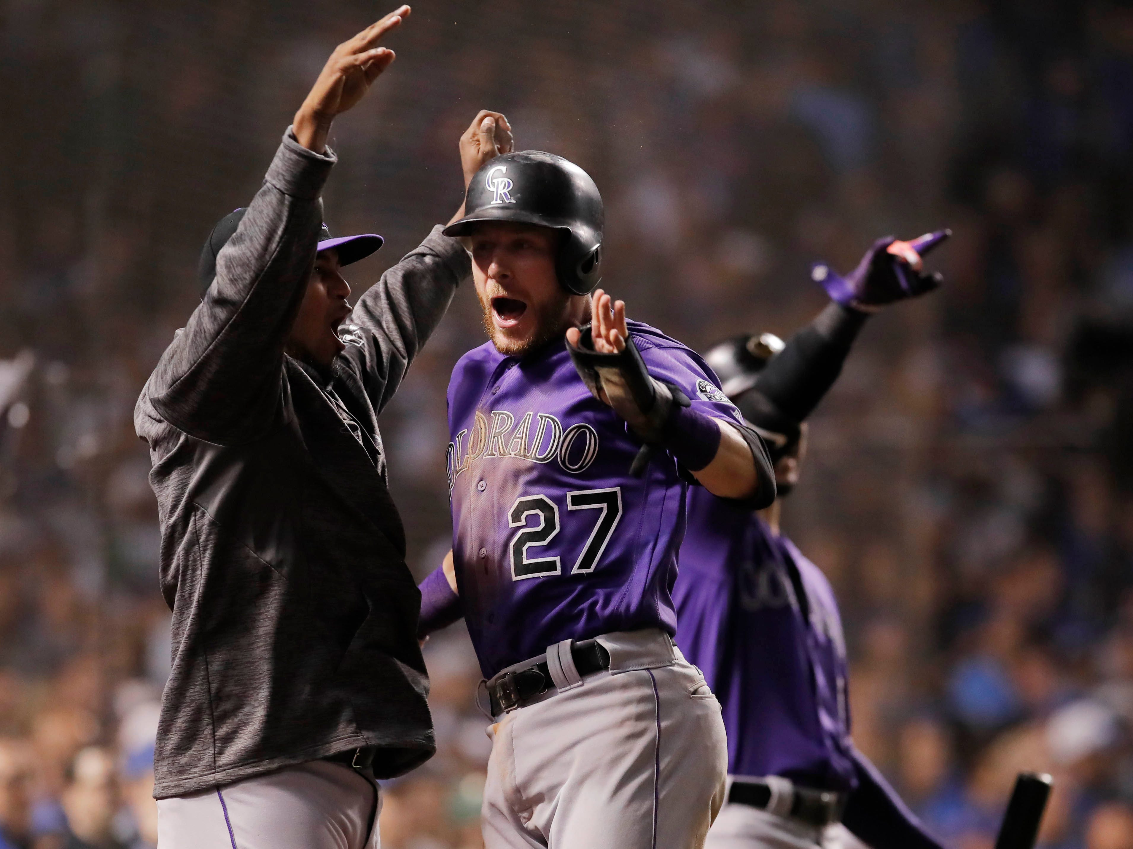 NL wild card: Rockies shortstop Trevor Story celebrates after scoring the go-ahead run in the 13th inning.