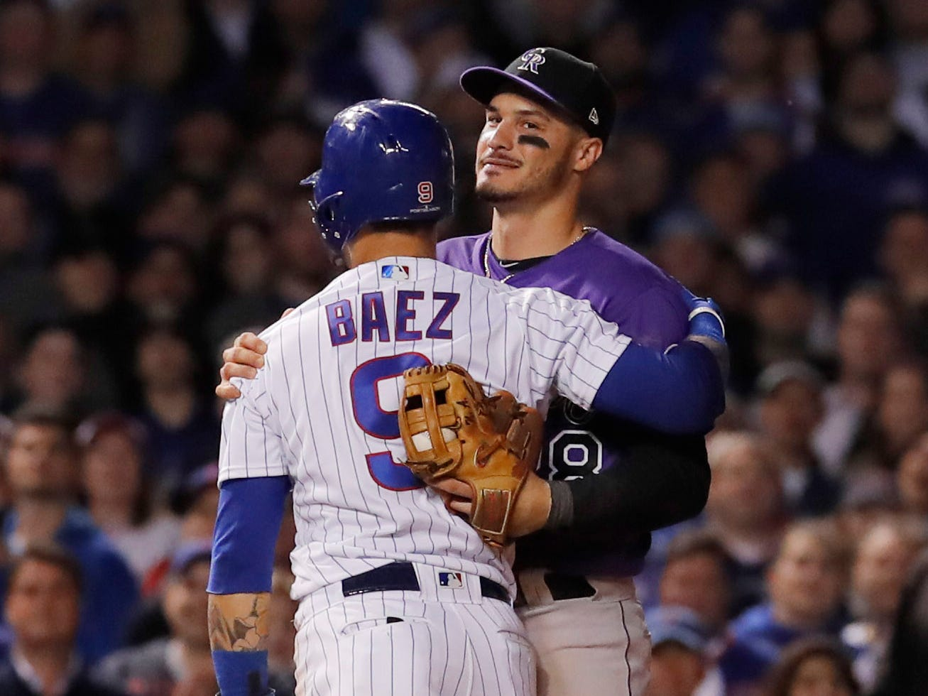 NL wild card: Cubs shortstop Javier Baez hugs Rockies third baseman Nolan Arenado after being tagged out in the 11th inning.
