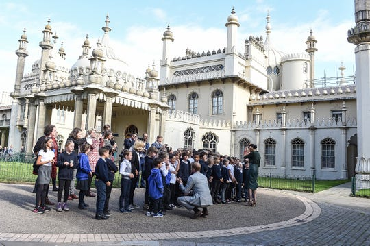 Prince Harry and Duchess Meghan of Sussex greet local school children front of the iconic Royal Pavilion in Brighton during an official visit to Sussex on Oct. 3, 2018, in southeast England.