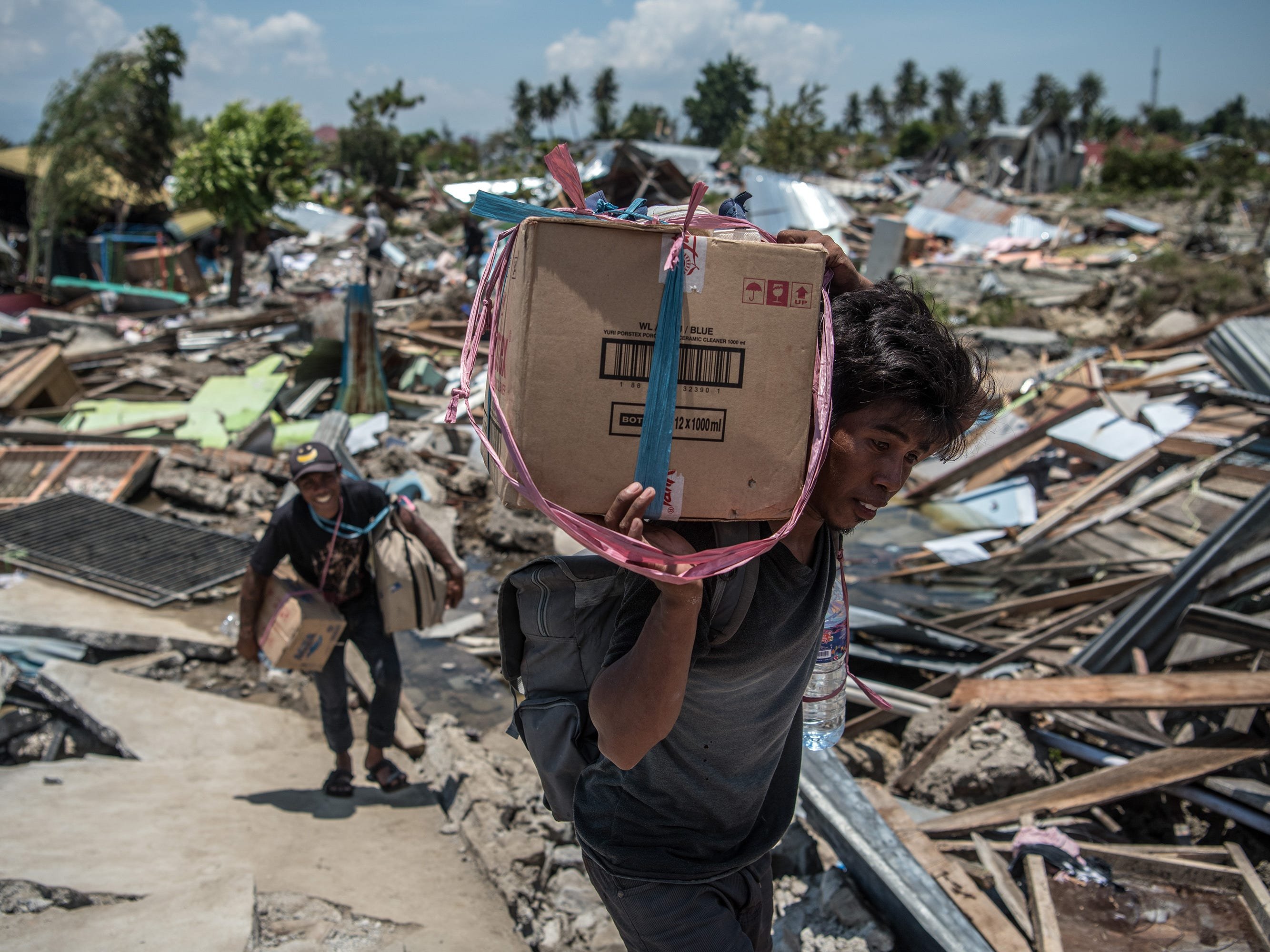 A man carries salvaged items through the rubble of buildings that were destroyed by an earthquake, on Oct. 02, 2018, in Palu, Indonesia.
