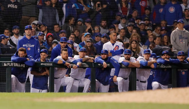 NL wild card: Cubs players look on from the dugout after the Rockies took a 2-1 lead in the bottom of the 13th inning.