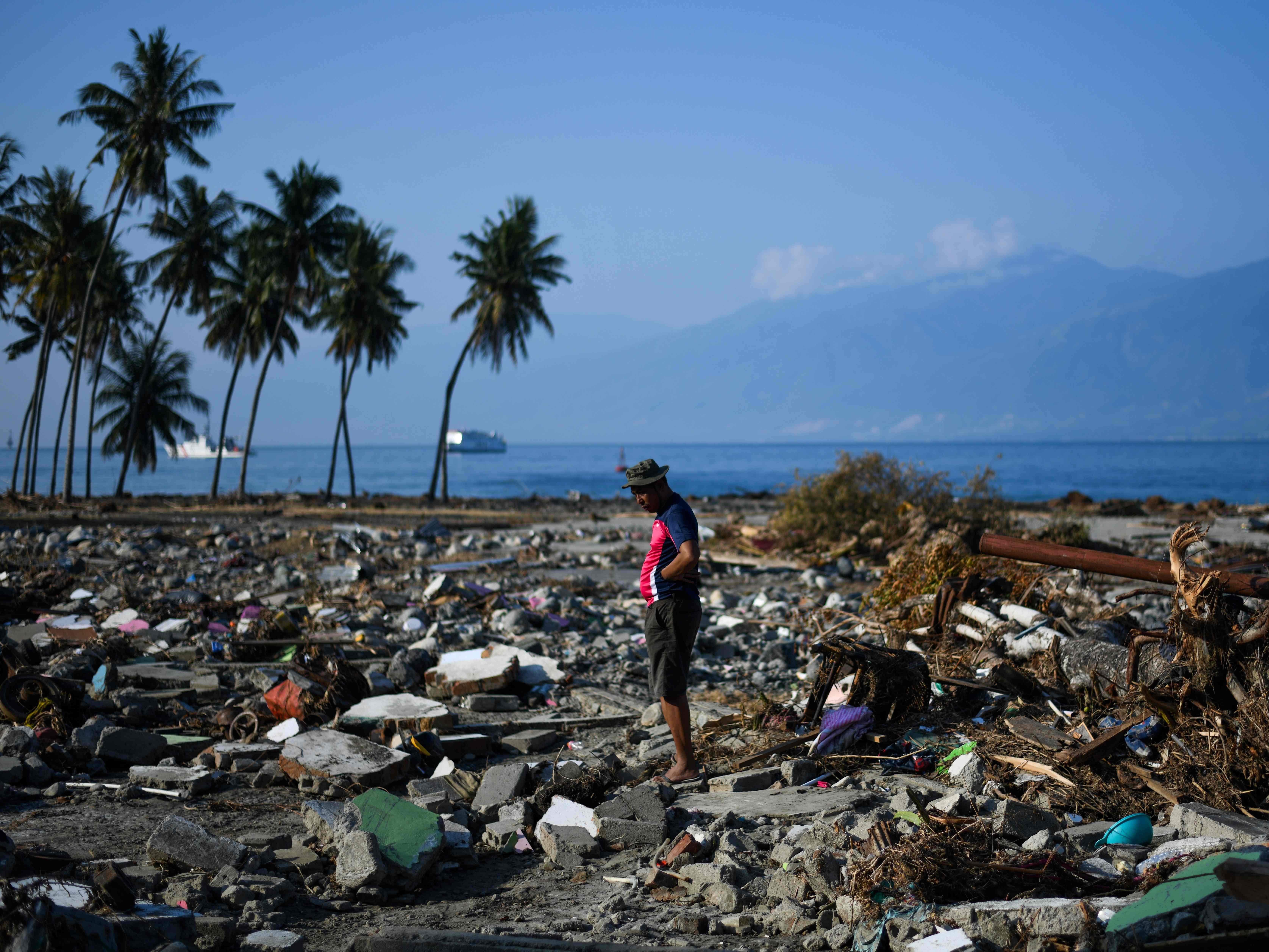 A quake survivor stands among debris in Wani, Indonesia's Central Sulawesi Oct. 3, 2018, after an earthquake and tsunami hit the area on Sept. 28.
