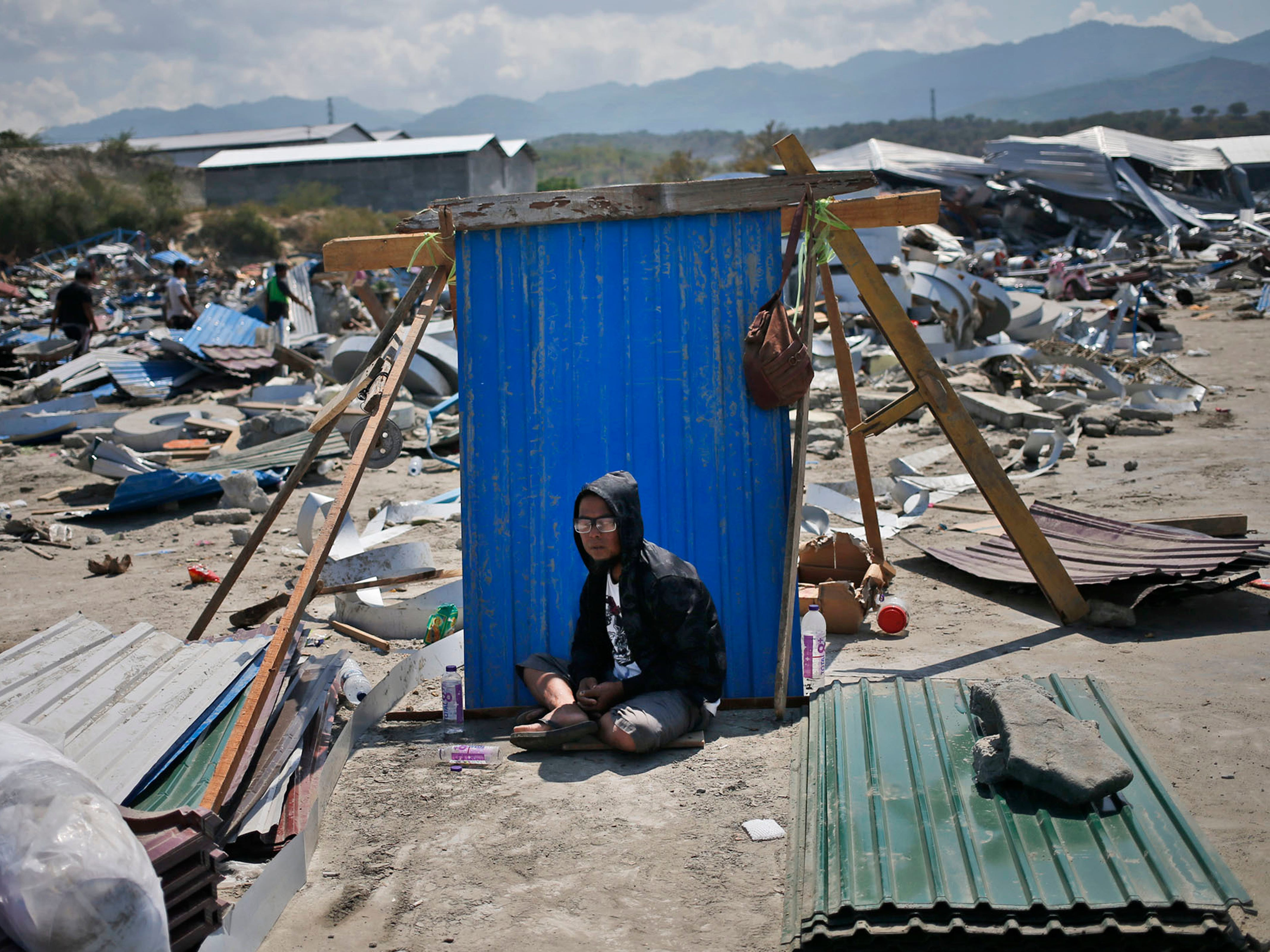 A man sits in the shade of a sheet of a corrugated tin surrounded by earthquake debris in Palu, Central Sulawesi, Indonesia. Oct. 3, 2018.