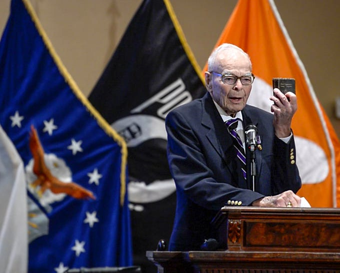 Living Prisoner of War 1st Lt. Bill Funchess holds up his Holy Bible he carried for 1,038 days while captured by the North Korean Army, telling the audience in Tillman Hall at Clemson University  on Thursday.
