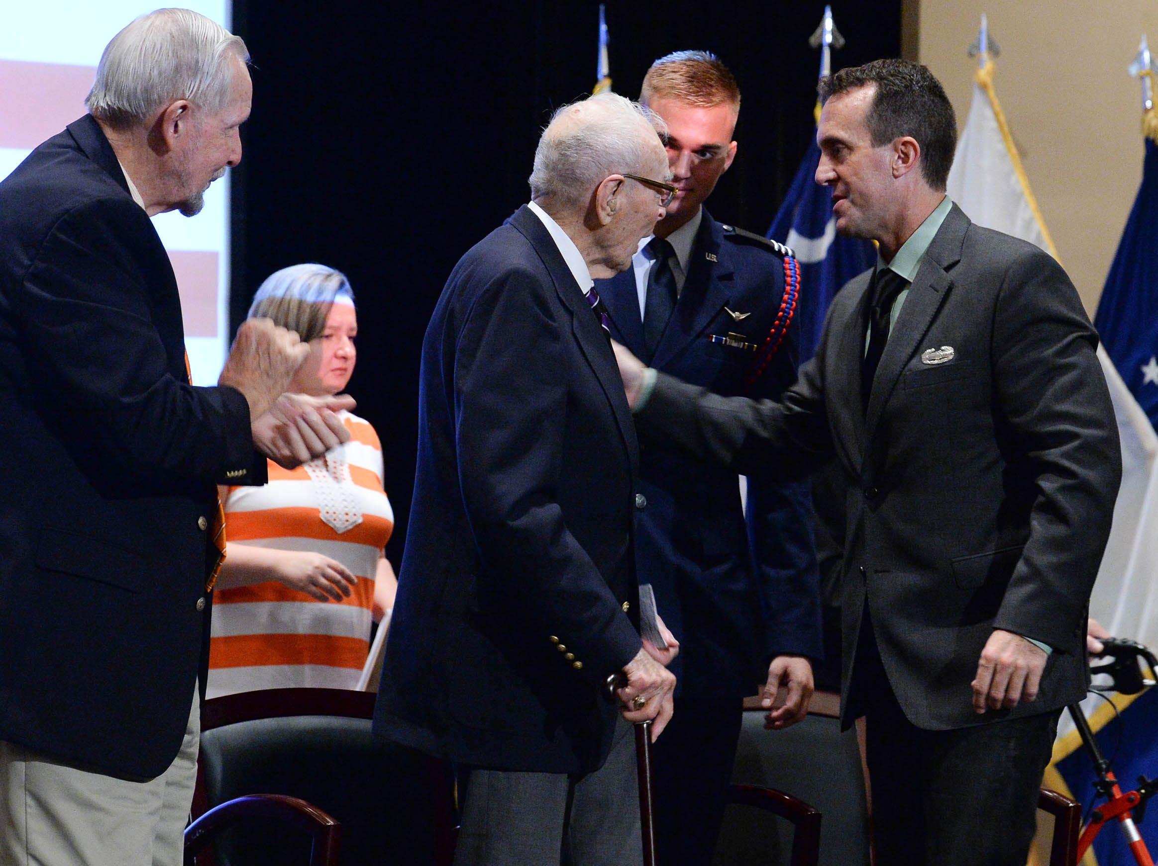 Living Prisoner of War 1st Lt. Bill Funchess, middle, is greeted by Ken Scar, right, near Col. Bill Austin spoke in Tillman Hall at Clemson University  on Thursday.