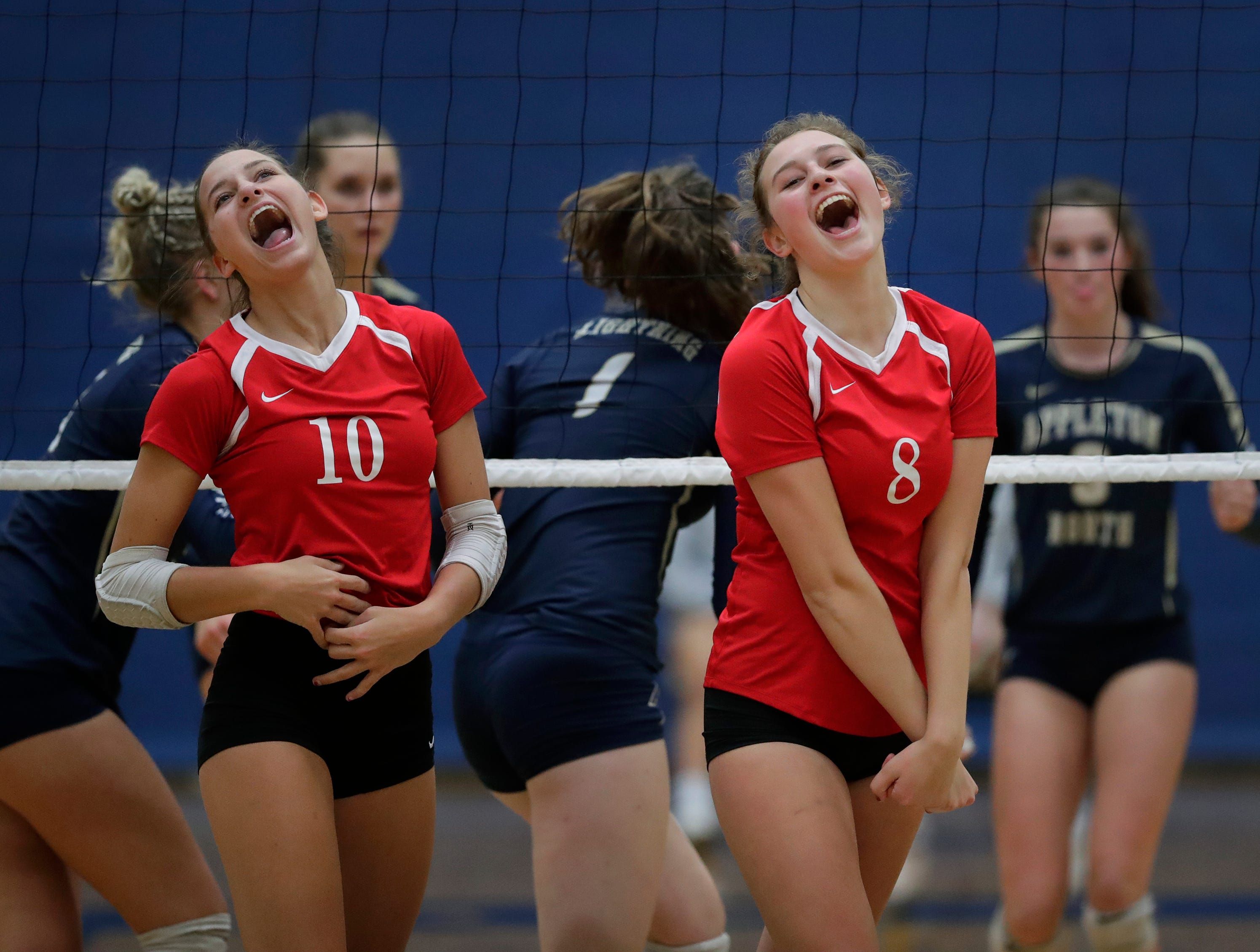 Kimberly High School's Courtney Pearson (10) and Carlee Doering (8) celebrate winning a point against Appleton North High School during their girls volleyball match Thursday, Sept. 27, 2018, in Appleton, Wis. 