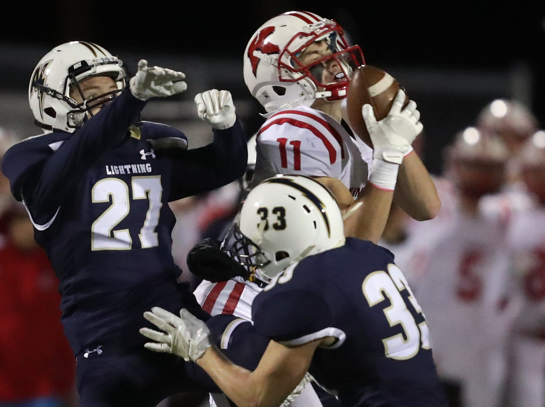 Kimberly High School's #11 Conner Wnek catches a pass over the defense of Appleton North High School's #27 Tyler Birling and #33 Devin Blom during their football game on Friday, September 28, 2018, at Paul Engen Field in Appleton, Wis. Kimberly defeated North 35 to 25Wm. Glasheen/USA TODAY NETWORK-Wisconsin.