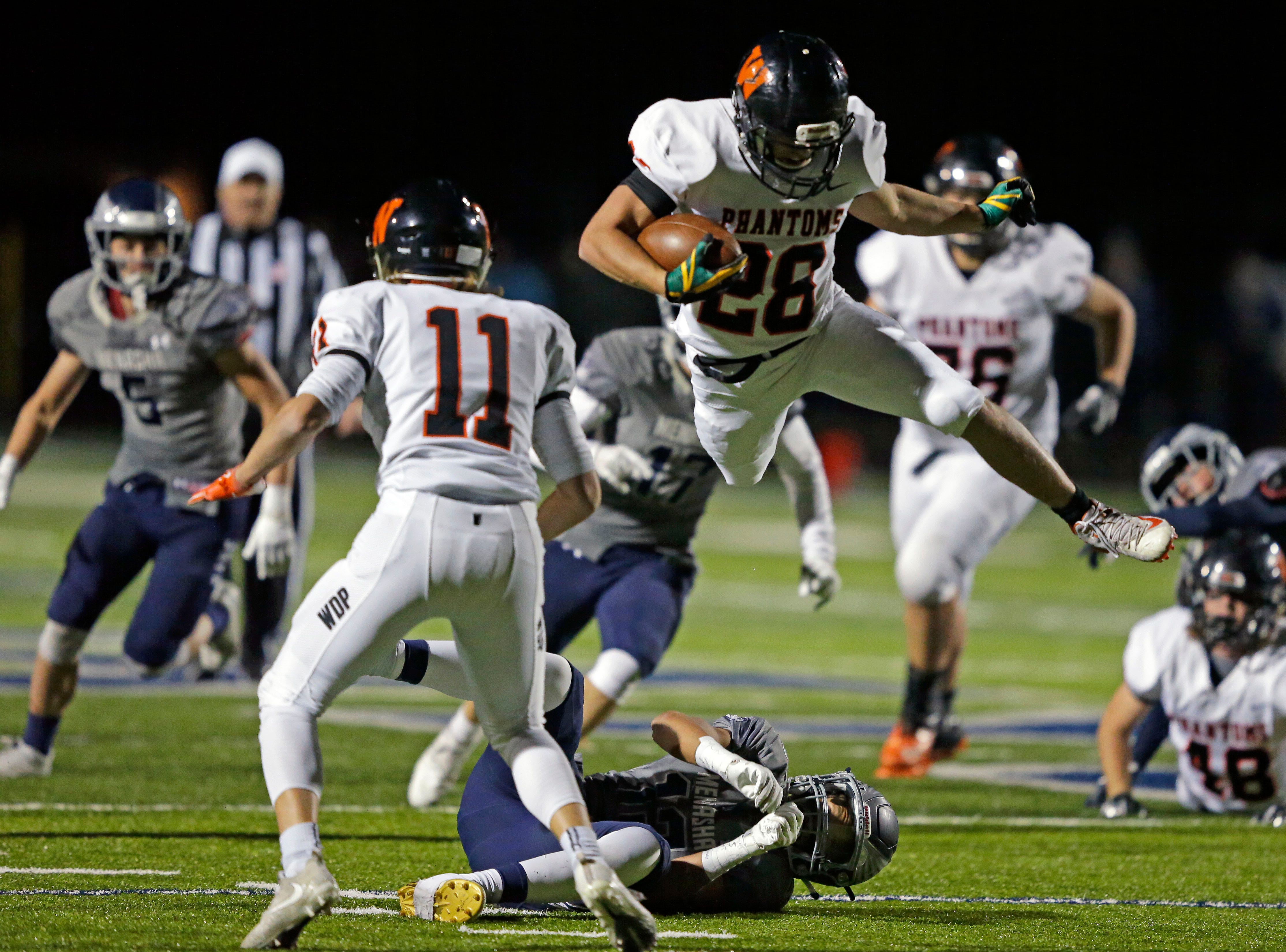 David Vanderlogt of West De Pere leaps over Leviathian Fleming of Menasha in a Bay Conference football game Friday, September 28, 2018, at Calder Stadium in Menasha, Wis.