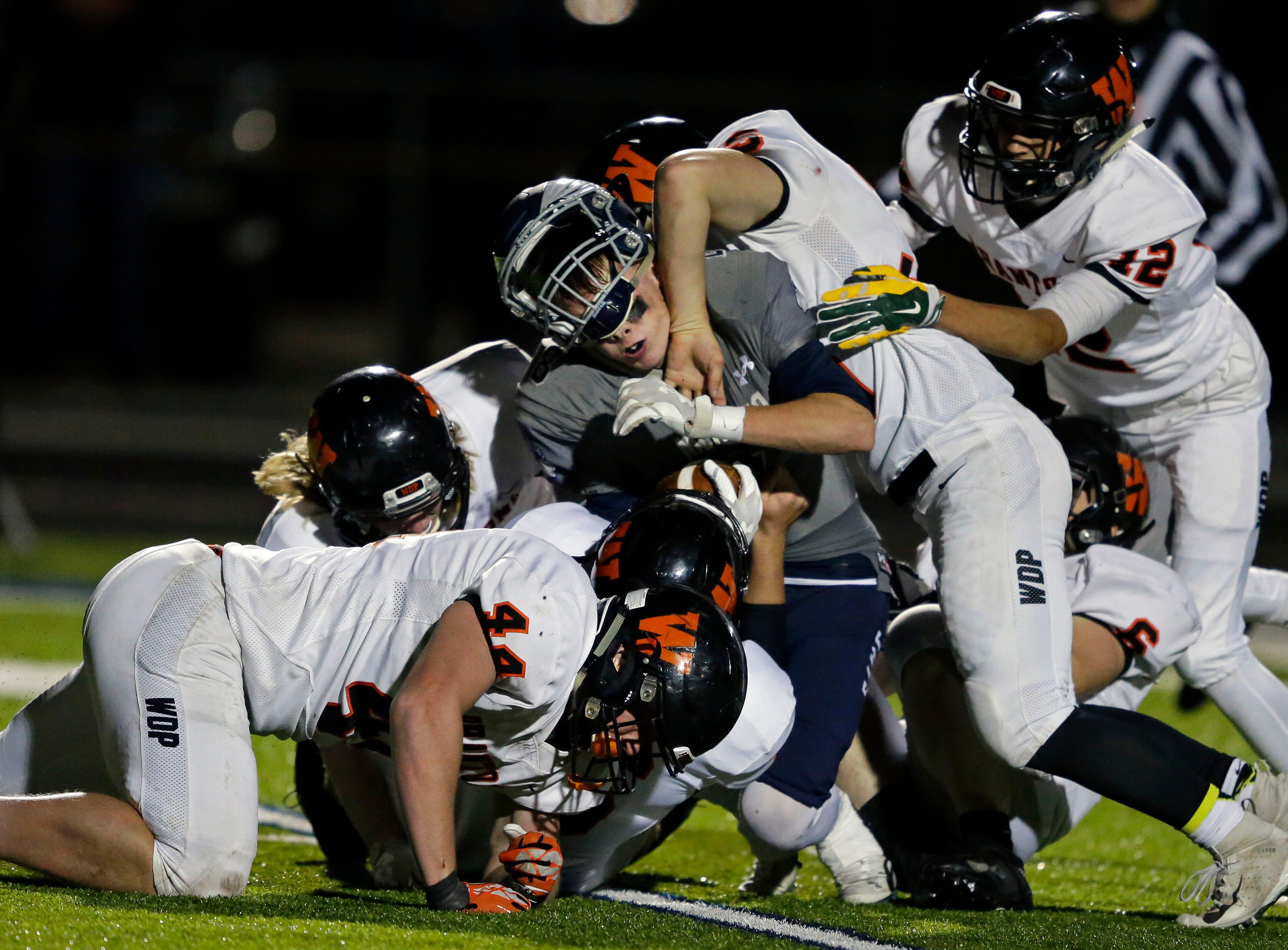 Brady Jurgella of Menasha loses his helmet as the West De Pere defense tackles him in a Bay Conference football game Friday, September 28, 2018, at Calder Stadium in Menasha, Wis.