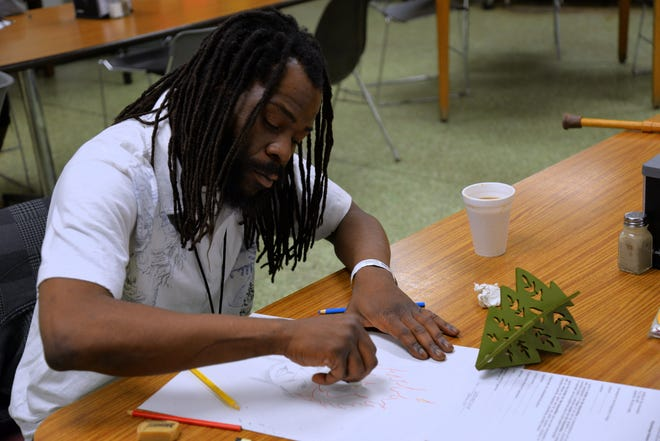 A participant of the Artists for the Humanities program works on drawing at VETS Place Central in Milwaukee.