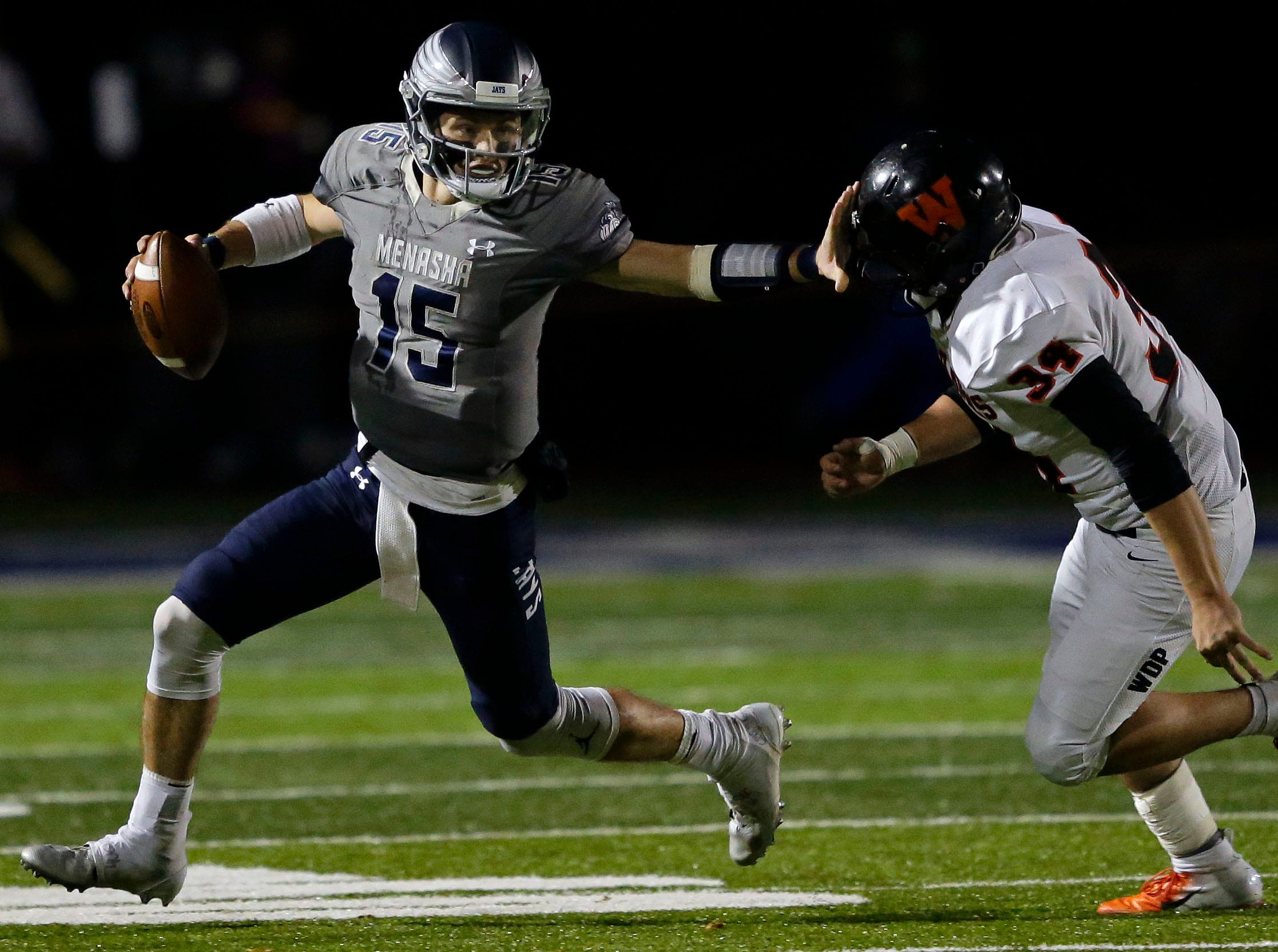 Quarterback Cole Popp of Menasha looks downfield while keeping away from Braydon Skenadore of West De Pere in a Bay Conference football game Friday, September 28, 2018, at Calder Stadium in Menasha, Wis.Ron Page/USA TODAY NETWORK-Wisconsin
