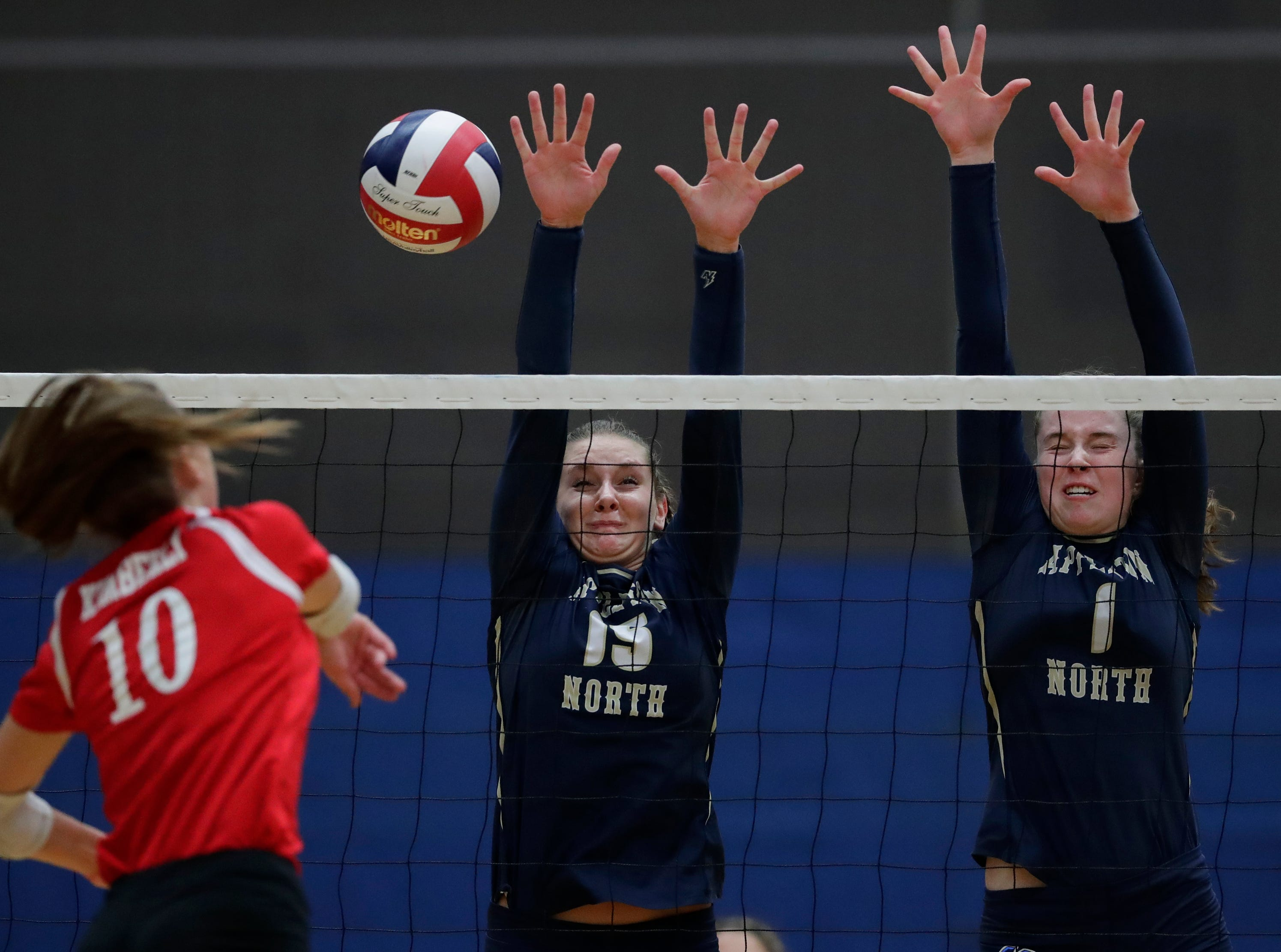 Kimberly High School's Courtney Pearson (10) spikes the ball against Appleton North High School's Taylor Vanden Berg (15) and Sarah Ganser (10) during their girls volleyball match Thursday, Sept. 27, 2018, in Appleton, Wis. 
