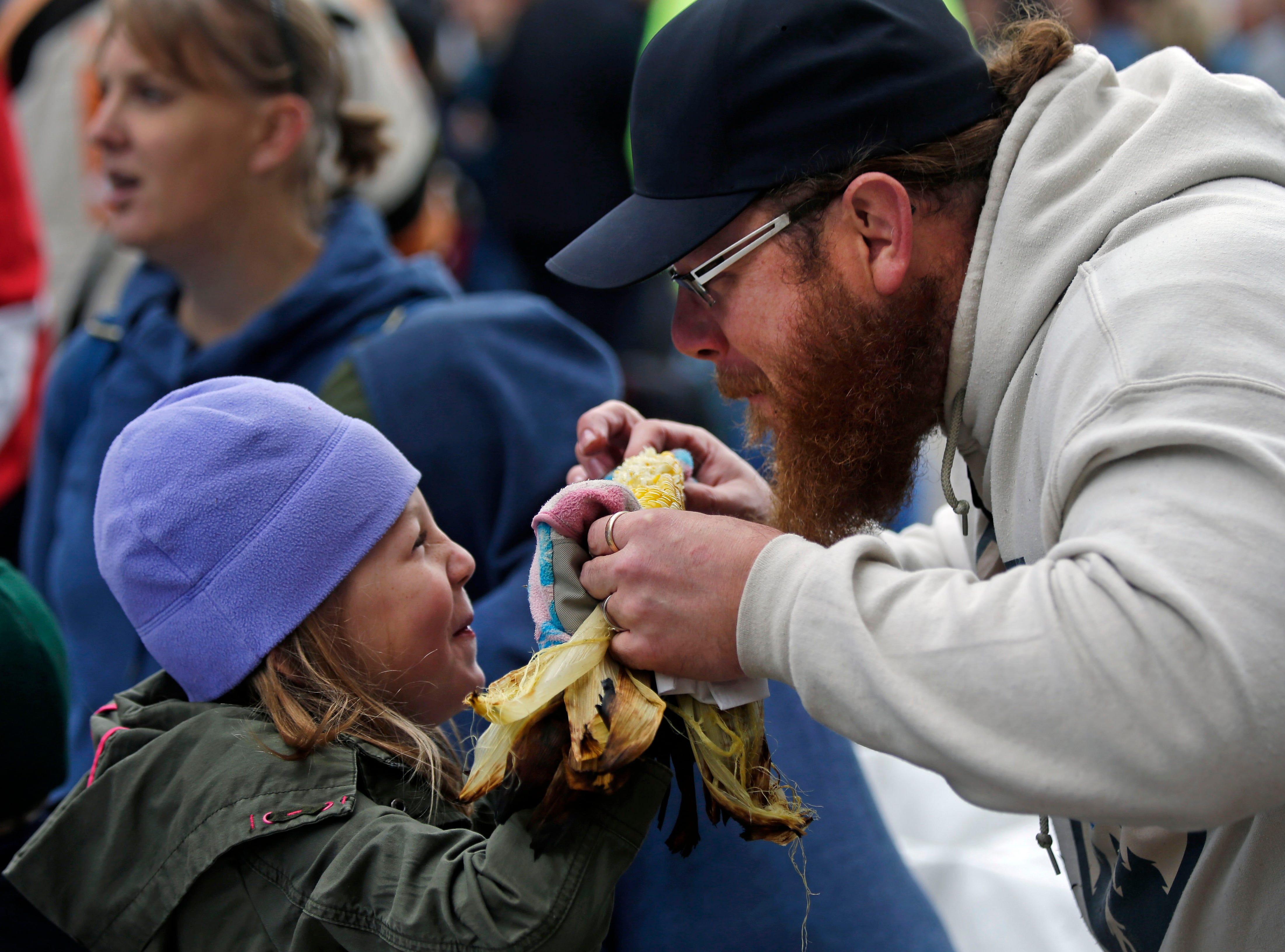 Matt Bonson and his daughter Zoe share corn on the cob as Octoberfest 2018 takes place Saturday, September 29, 2018, in downtown Appleton, Wis.