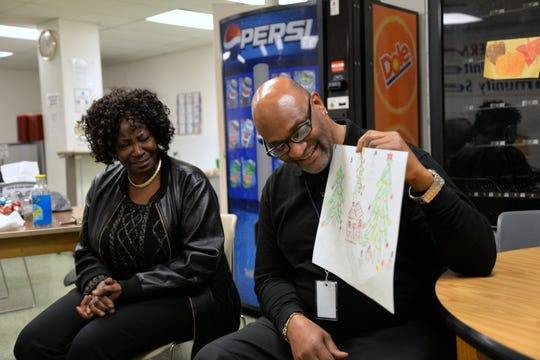 Debra Jeter, a social work, left, sits with a veteran who presents a drawing during a group session put on by Artists for the Humanities at VETS Place Central in Milwaukee.