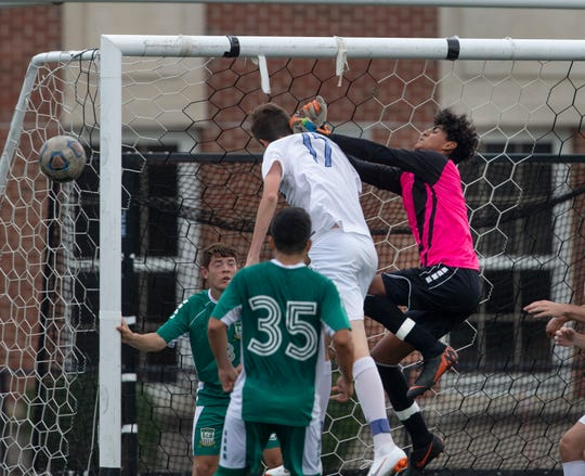 Long Branch goalie Rodolfo Giron knocks ball away from front of goal before Freehold's Connor Finn can head it into goal. Freehold Twp. Boys Soccers defeats Long Branch 3-1 in Long Branch NJ on October 4, 2018.