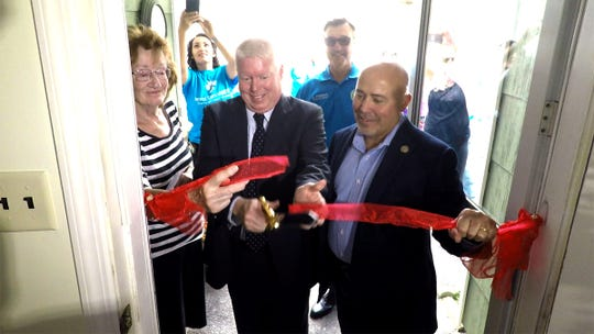 Markham Road resident Renate Kupatt (left) assists along with Congressman Tom MacArthur and Brick Mayor John Ducey cuts the ribbon at her refurbished home Thursday, October 4, 2018.  Her home was rebuilt by Jersey Shore United Inc., a faith based non-profit organization, after heavy rains flooded it in August.