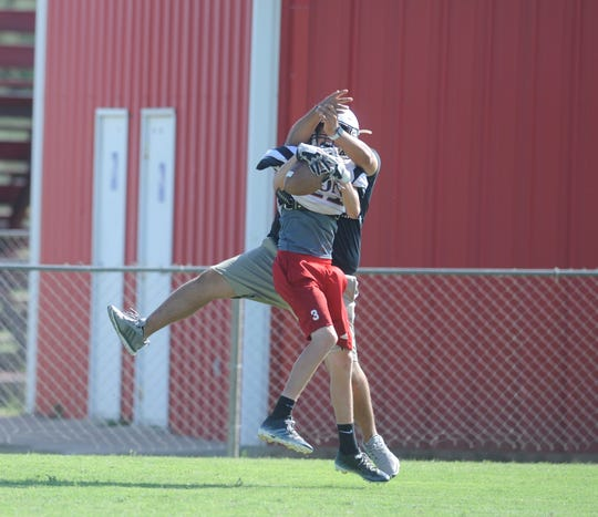 A Roby receiver makes a catch in front of assistant coach Johnny Sanchez during a practice Oct. 3, 2018. The Lions have to utilize coaches in unique ways because of low numbers.