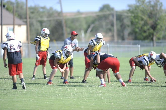 Roby assistant football coach Ryan Cronkright, center, prepares to take a snap during a practice Oct. 3, 2018. Because of low numbers, the Lions must utilize coaches in unique ways during practices.